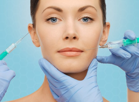 plastic surgery, injections and beauty concept - beautiful young woman face and surgeon hands with syringes over blue background