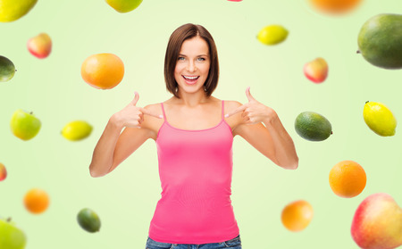 fingers on top: people, advertisement, diet, food and healthy eating concept - smiling woman in blank pink tank top pointing fingers to herself over fruits on green background