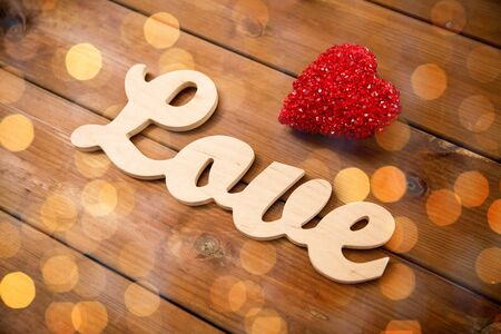 decoracion mesas: amor, fecha, romance, el día de San Valentín y concepto de vacaciones - cerca de la palabra amor con la decoración de corazón rojo en la madera Foto de archivo