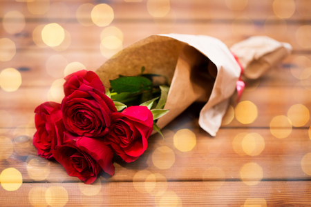 attentions: love, date, flowers, valentines day and holidays concept - close up of red roses bunch wrapped into brown paper on wooden table