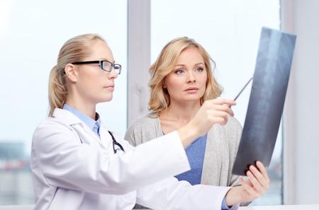 La medicina, la edad, la atención de la salud y el concepto de la gente - paciente de la mujer y el médico con columna vertebral exploración de rayos X reunión en la oficina médica