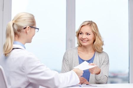 geneeskunde, gezondheidszorg, ontmoeting en mensen concept - glimlachend arts die medisch voorschrift of certificaat aan de vrouw in het ziekenhuis Stockfoto