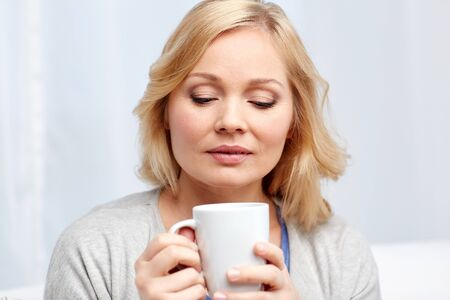 guessing: people, guesswork, drinks and leisure concept - woman with cup of tea or coffee at home
