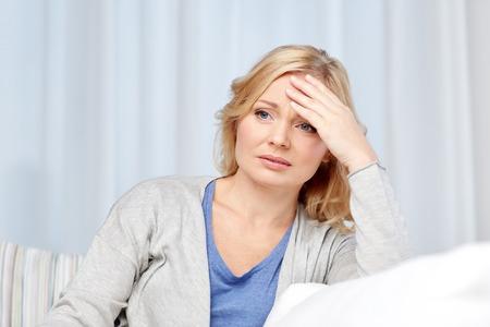 estrés: cuidado de la salud, el dolor, el estrés y las personas concepto - mujer de mediana edad que sufre de dolor de cabeza en el hogar Foto de archivo