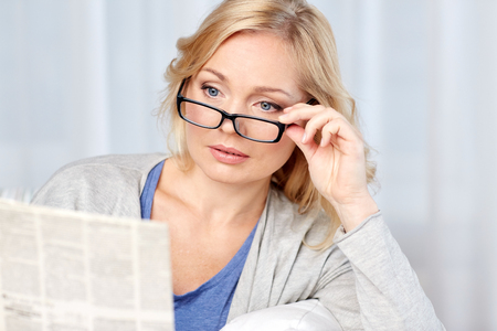 middle age: news, press, media, leisure and people concept - woman in eyeglasses reading newspaper at home Stock Photo