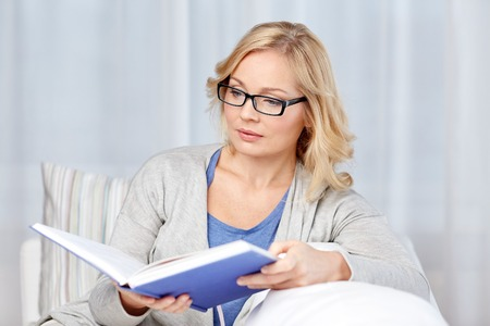 living wisdom: leisure, literature and people concept - middle aged woman reading book and sitting on couch at home