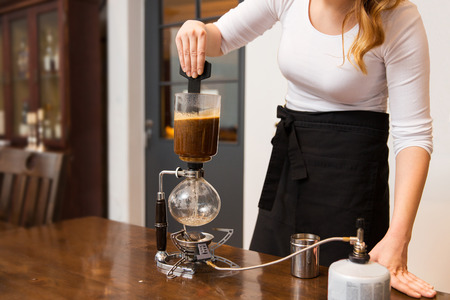 siphon: equipment, coffee shop, people and technology concept - close up of woman stirring coffee grounds in siphon coffeemaker top vessel at cafe bar or restaurant kitchen