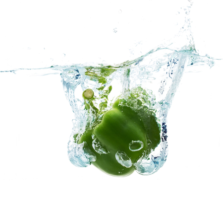 pimenton: vegetables, food and healthy eating concept - close up of fresh green pepper falling or dipping in water with splash over white background