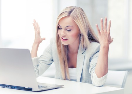 picture of angry businesswoman with laptop at work Stock Photo