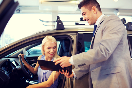 rental: auto business, car sale, consumerism and people concept - happy woman with car dealer in auto show or salon Stock Photo