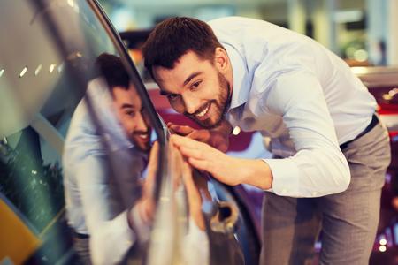 negocio de autos, venta de coche, el consumismo y el concepto de la gente - hombre feliz tocando coche en salón del automóvil o el salón Foto de archivo