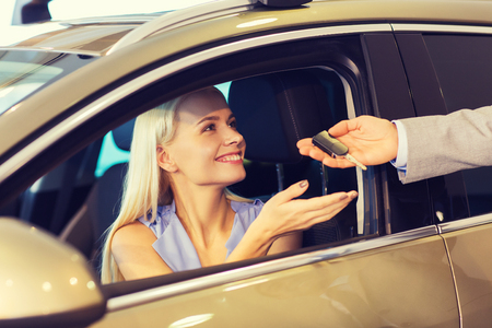car service: auto business, car sale, consumerism and people concept - happy woman taking car key from dealer in auto show or salon
