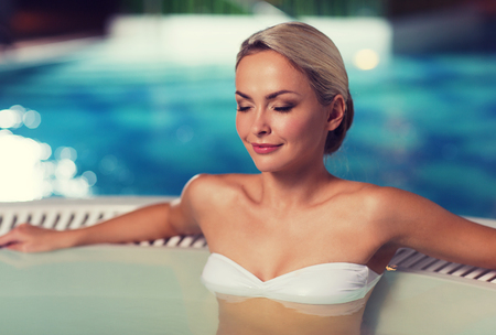 indoor: people, beauty, spa, healthy lifestyle and relaxation concept - beautiful young woman wearing bikini swimsuit sitting in jacuzzi at poolside Stock Photo