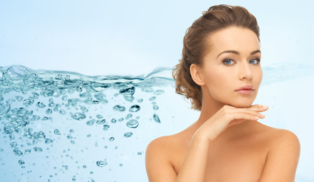 face female: beauty, people, moisturizing and health concept - smiling young woman with bare shoulders touching her face over water splash on blue background Stock Photo