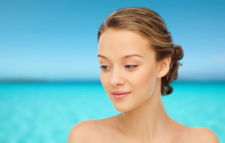teen girl smile face: beauty, people and health concept - smiling young woman face and shoulders over blue sea and sky background