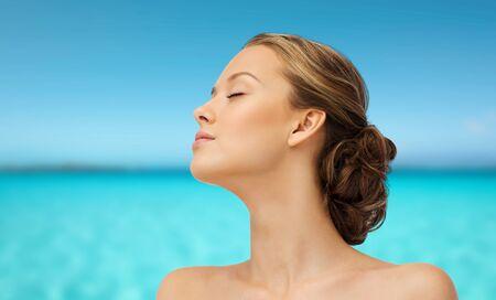 Schönheit, Menschen, Sommer, Hautpflege und Gesundheit Konzept - Gesicht der jungen Frau mit geschlossenen Augen Liegeseitenansicht über blauem Meer und Himmel im Hintergrund