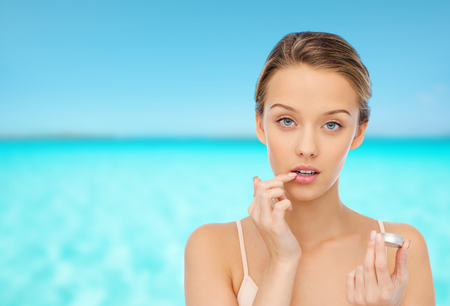 beauty, people and lip care concept - young woman applying lip balm to her lips over blue sea and sky background Stock Photo