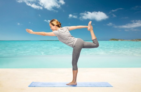 beach mat: fitness, sport, people and healthy lifestyle concept - woman making yoga in lord of the dance pose on mat over beach background