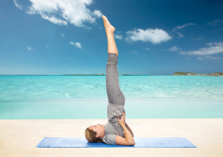 beach mat: fitness, sport, people and healthy lifestyle concept - woman making yoga in shoulderstand pose on mat over beach background Stock Photo