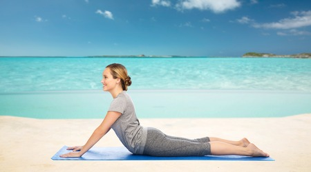 dog pose: fitness, sport, people and healthy lifestyle concept - woman making yoga in dog pose on mat over sea and sky background Stock Photo