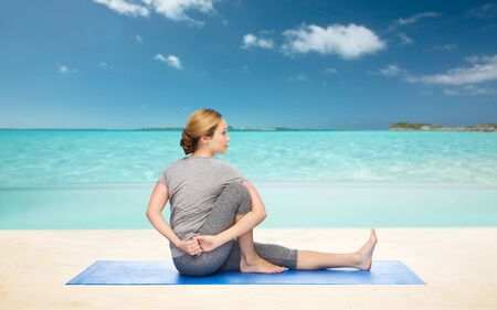 beach mat: fitness, sport, people and healthy lifestyle concept - woman making yoga in twist pose on mat over beach background