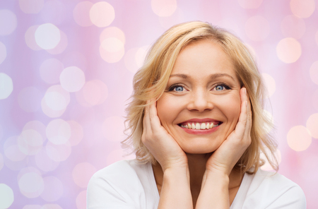 touching face: beauty, people and skincare concept - smiling middle aged woman in white shirt touching face over pink holidays lights background