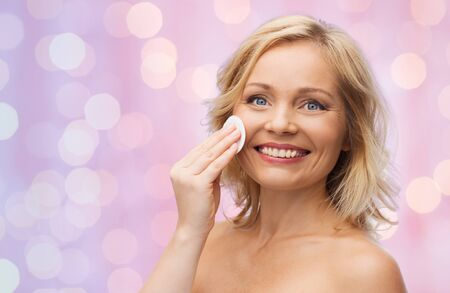 removing make up: beauty, people and skincare concept - happy middle aged woman cleaning face and removing make up with cotton pad over pink holidays lights background