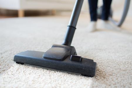 自宅のカーペットのクリーニングの足掃除機で女のクローズ アップ人、家事やハウスキーピングのコンセプト-