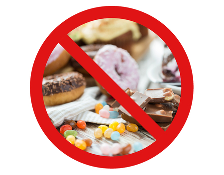 low carb diet: fast food, low carb diet, fattening and unhealthy eating concept - close up of chocolate pieces, jelly beans and glazed donuts behind no symbol or circle-backslash prohibition sign