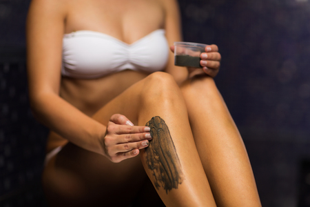 mud woman: people, beauty, spa, healthy lifestyle and relaxation concept - close up of woman applying therapeutic mud to her body in bath