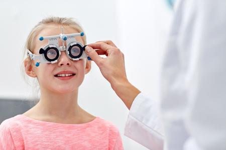 soins de santé, la médecine, les gens, la vue et le concept de la technologie - optométriste avec monture d'essai vérifiant fille vision du patient à la clinique des yeux ou optiques magasin