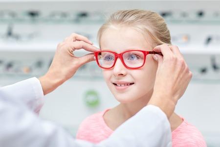 건강 관리, 사람, 시력과 비전 개념 - 광학 가게에서 어린 소녀의 눈에 안경점 퍼팅 안경 스톡 콘텐츠
