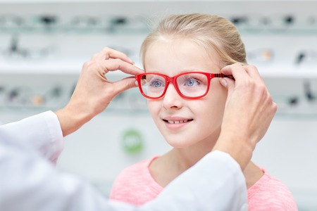 health care, people, eyesight and vision concept - optician putting glasses to little girl eyes at optics store Stockfoto