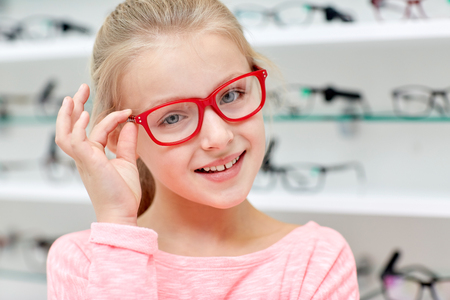 health care, people, eyesight and vision concept - little girl in glasses at optics store Stock Photo