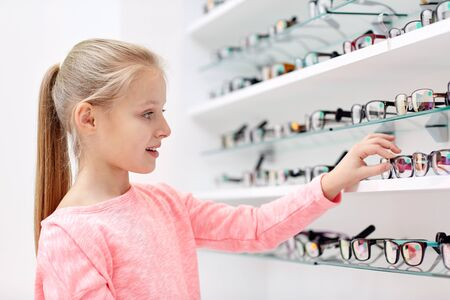 glasses eye: health care, people, eyesight and vision concept - little girl choosing glasses at optics store