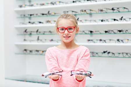 health care, people, eyesight and vision concept - little girl in glasses at optics store Imagens