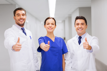 thumbsup: profession, people, health care, gesture and medicine concept - group of happy medics or doctors at hospital corridor showing thumbs up