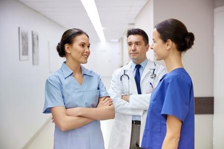personas dialogando: clínica, profesión, las personas, la salud y concepto de la medicina - grupo de médicos o médicos felices de reuniones y hablando en el pasillo del hospital
