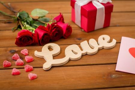 uprzejmości: romans, Walentynki i święta koncepcji - bliska słowa miłości, pudełko, czerwonych róż i kartkę z życzeniami z serca w kształcie cukierków na drewnie Zdjęcie Seryjne