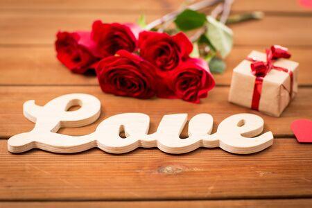 uprzejmości: miłość, romans, Walentynki i święta pojęcie - zamknąć pudełko, czerwone róże i serca na drewnie Zdjęcie Seryjne