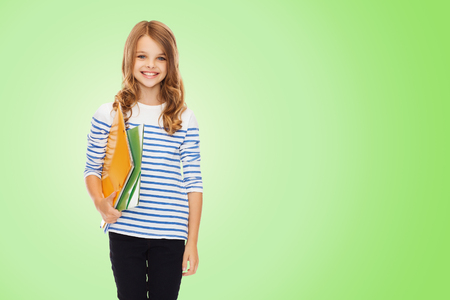 pre teens: education, people, children and school concept - happy girl holding colorful folders over green background