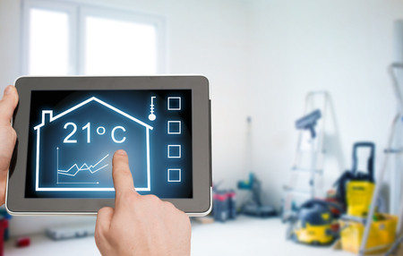 regulating: home, housing, people and technology concept - close up of man hands pointing finger to tablet pc computer and regulating room temperature over storeroom or building background