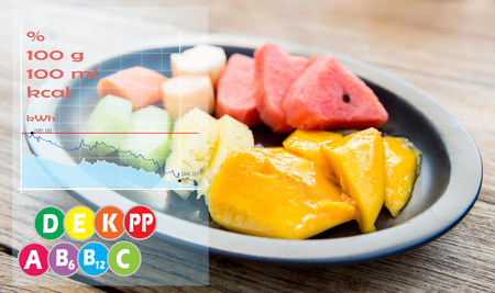 cooking, kitchen and food concept - plate of fresh juicy fruits with calories and vitamin chart Stock Photo