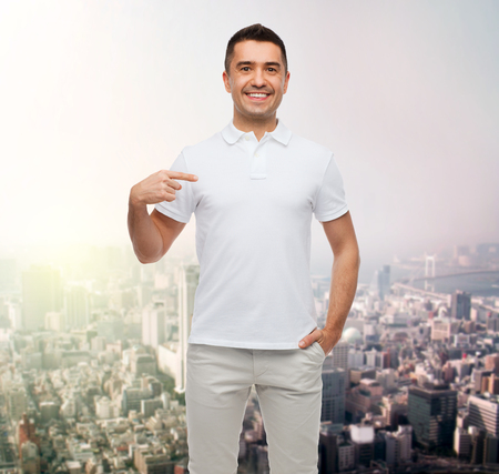 gestures: happiness, advertisement, fashion, gesture and people concept - smiling man in t-shirt pointing finger on himself over city background