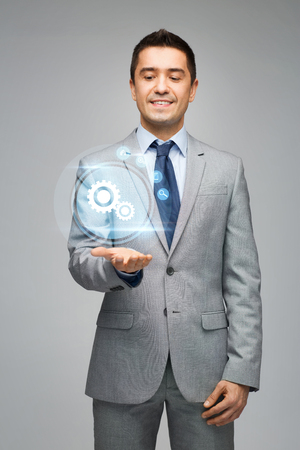 background settings: business, people and technology concept - happy businessman in suit showing or holding virtual projection of computer settings on hand palm over gray background