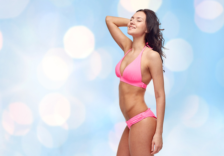 model nice: people, fashion, swimwear, summer and beach concept - happy young woman posing in pink bikini swimsuit over blue holidays lights background
