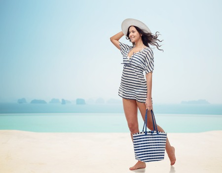 fashion clothes: people, fashion, summer and beach concept - happy young woman in summer clothes and sun hat with bag over infinity pool at beach resort