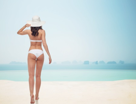 people, fashion, swimwear, summer beach and beauty concept - young woman in white bikini swimsuit from back over infinity pool at beach resort Stock Photo