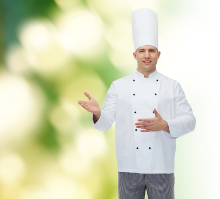 inviting: cooking, profession and people concept - happy male chef cook inviting over green background