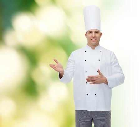 invitando: la cocina, la profesi�n y el concepto de la gente - cocinero de sexo masculino feliz cocinar invitando sobre fondo verde Foto de archivo